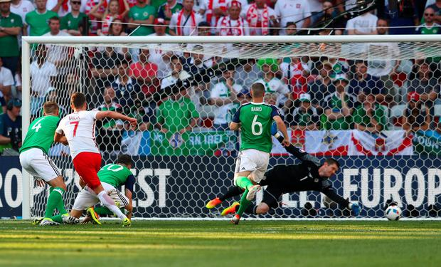 Cruel blow: Arkadiusz Milik of Poland scores his team's winning goal past Michael McGovern of Northern Ireland