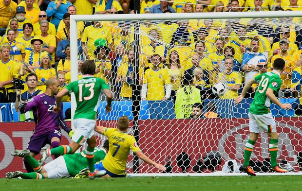 Bitter blow: Republic of Ireland defender Ciaran Clark (second left) falls on the pitch as he scores the own goal that gave Sweden a draw