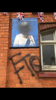 The defaced portrait of Her Majesty The Queen and graffiti placed on Derriaghy Orange Hall near Lisburn