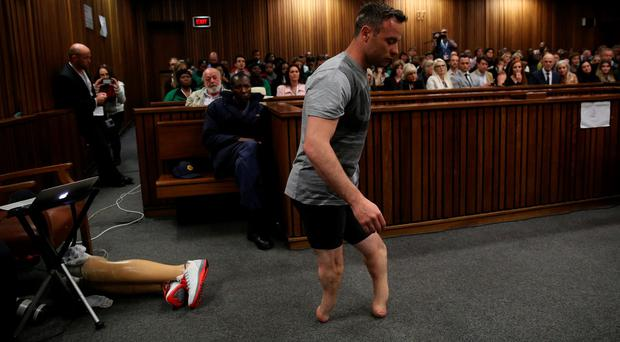 Oscar Pistorius' prosthetics lay on the floor as he walks on his stumps during argument in mitigation of sentence by his defense attorney Barry Roux in the High Court in Pretoria, South Africa, Wednesday, June 15, 2016. An appeals court found Pistorius guilty of murder and not a lesser charge of culpable homicide for the shooting death of his girlfriend Reeva Steenkamp. (Siphiwe Sibeko, Pool Photo via AP)