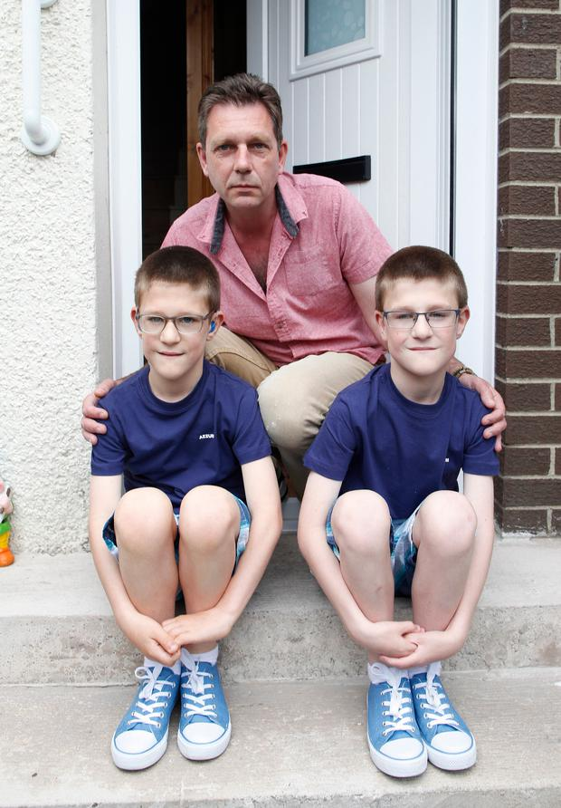 Proud father: David Baker has given up work to look after his twin sons Scott, (left) and Michael
