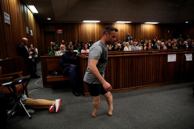 Pistorius walks in the courtroom after removing his prosthetic legs