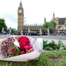"Flowers left at Parliament Square opposite the Palace of Westminster, central London, following the death of Labour MP Jo Cox, who died after being shot and stabbed in the street outside her constituency advice surgery in Birstall, West Yorkshire. PRESS ASSOCIATION Photo. Picture date: Thursday June 16, 2016. The alleged gunman has been named locally as Tommy Mair, 52, who neighbours in Birstall have described as ""a loner"". See PA story POLICE MP. Photo credit should read: Philip Toscano/PA Wire"