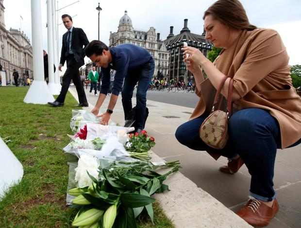 Flowers left at Parliament Square opposite the Palace of Westminster, central London, following the death of Labour MP Jo Cox, who died after being shot and stabbed in the street outside her constituency advice surgery in Birstall, West Yorkshire. PRESS ASSOCIATION Photo. Picture date: Thursday June 16, 2016. The alleged gunman has been named locally as Tommy Mair, 52, who neighbours in Birstall have described as