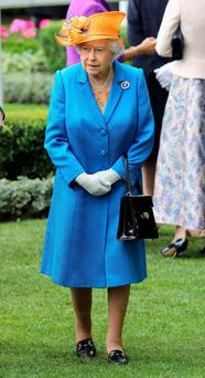 The Queen, who wore a striking orange hat and cobalt blue coat, joined throngs of spectators for Ladies' Day. (Photo by Chris Jackson/Getty Images)