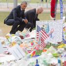 US President Barack Obama and Vice President Joe Biden pause after laying flowers for the victims of the mass shooting in Orlando. Saul Loeb/AFP/Getty Images