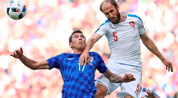 Croatia's Mario Mandzukic, left, and Czech Republic's Roman Hubnik go for the ball during the Euro 2016 Group D soccer match between the Czech Republic and Croatia at the Geoffroy Guichard stadium in Saint-Etienne, France, Friday, June 17, 2016. (AP Photo/Laurent Cipriani)