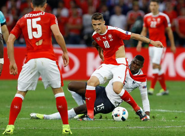 Letting rip: Swiss midfielder Granit Xhaka plays on with a torn shirt