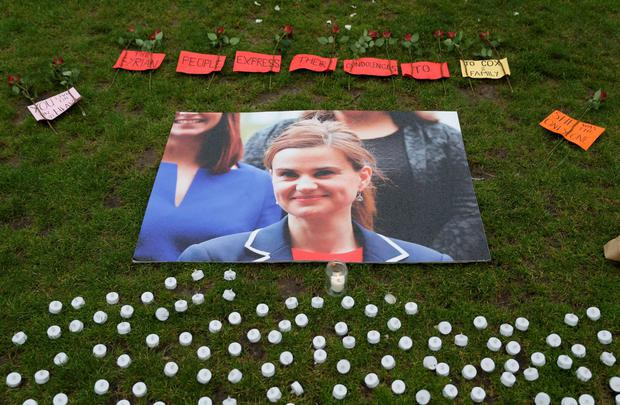 A picture shows tributes laid by the Syria Solidarity Campaign during a vigil in remembrance of slain Labour MP Jo Cox (photo) in Parliament Square in front of the Houses of Parliament in central London on June 19, 2016. British MP Jo Cox was on Sunday remembered as a