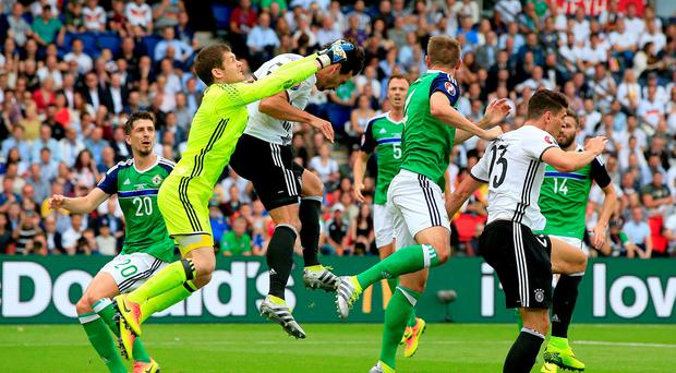 Northern Ireland goalkeeper Michael McGovern (left) punches clear from the head of Germany's Mats Hummels (centre) during the UEFA Euro 2016, Group C match at the Parc Des Princes, Paris. Jonathan Brady/PA Wire.
