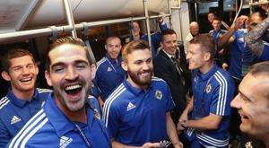 Northern Ireland players get the news they were waiting on that they have qualified out of their Euro 2016 group. They were on an airport bus to their plane at Charles de Gaulle airport where they flew back to Lyon.