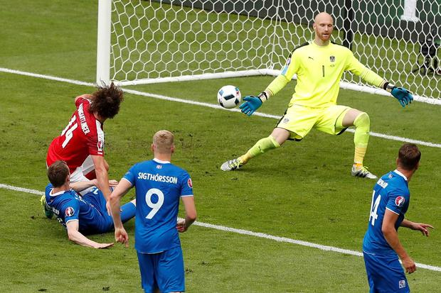 Iceland's Jon Dadi Bodvarsson, left, shoots to score past Austria goalkeeper Robert Almer, top, during the Euro 2016 Group F soccer match between Iceland and Austria at the Stade de France in Saint-Denis, north of Paris, France, Wednesday, June 22, 2016. (AP Photo/Francois Mori)