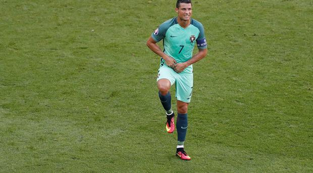 Portugal's Cristiano Ronaldo reacts after jumping for the ball during the Euro 2016 Group F soccer match between Hungary and Portugal at the Grand Stade in Decines-Charpieu, near Lyon, France, Wednesday, June 22, 2016. (AP Photo/Michael Sohn)