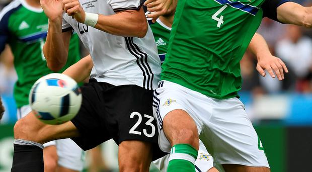 Northern Ireland's Gareth McAuley battles Germany's Mario Gomez for the ball during the Group C match in Paris, France. The IFA is set to make an extra £2m after Northern Ireland claimed their last-16 place in the Euros after the match