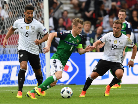 Leading the way: Steven Davis in action with Germany's Sami Khedira and Mario Gotze, who he swapped shirts with afterwards