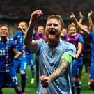 You beauty: Iceland's Aron Gunnarsson (centre) leads his side's celebrations after the historic victory over England last night