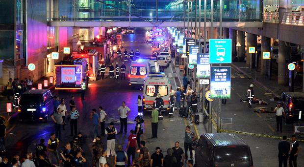 Medics and security members work at the entrance of the Ataturk Airport after explosions in Istanbul, Tuesday, June 28, 2016. (IHA via AP)
