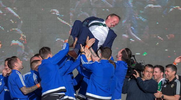 Highs and lows: Northern Ireland boss Michael O'Neill is given the bumps by his players at the team's homecoming