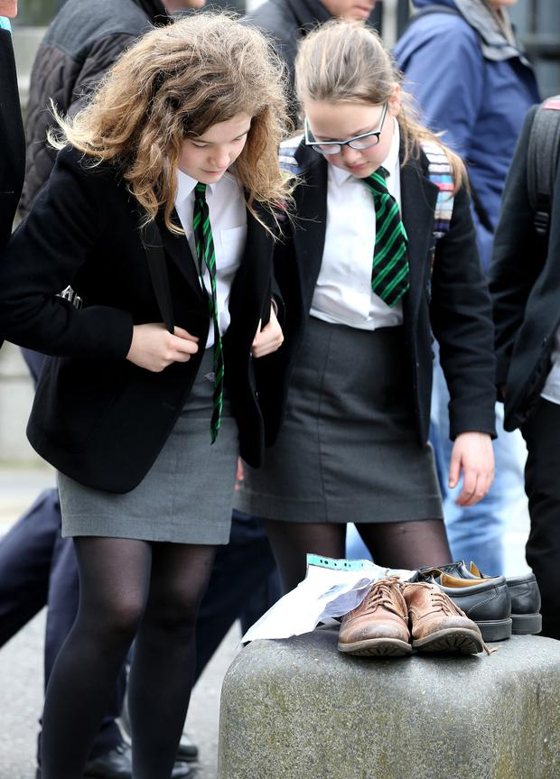 Schoolgirls look at shoes belonging to victims of the Troubles left by their relatives during a protest outside court in Belfast yesterday