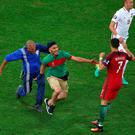 Pitch invasion: Cristiano Ronaldo is confronted by a Portugal fan