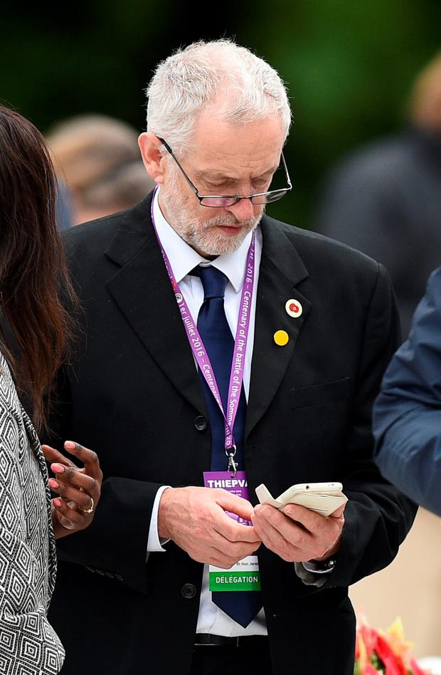 Labour Party leader Jeremy Corbyn checks his phone during the Commemoration of the Centenary of the Battle of the Somme at the Commonwealth War Graves Commission Thiepval Memorial on July 1, 2016 in Thiepval, France. (Photo by Andrew Matthews - Pool/Getty Images)