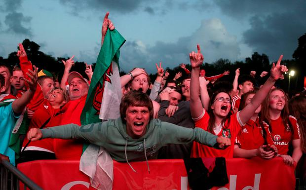 Wales fans celebrate after Wales score their third goal at a screening of the Euro 2016 quarter final match between Wales and Belgium at the fan zone in Cardiff, south Wales on July 1, 2016. / AFP PHOTO / Geoff CADDICKGEOFF CADDICK/AFP/Getty Images