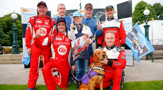 Taking the lead : Lurgan Park Rally winner Garry Jennings,front centre, and his team with fan Christian Patterson (9), from East Belfast, and his helper dog Rowan. Photo: Kevin Scott/Presseye
