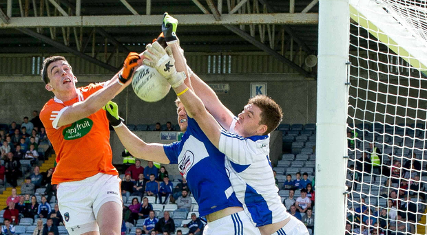 High fyler: Armagh's Rory Grugan scores a goal despite the close attention of Mark Timmons and Graham Brody of Laois. Photo: Morgan Treacy/INPHO