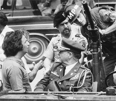 Director Michael Cimino, left, talks with actor Robert De Niro (wearing beret) during a break in the filming of The Deer Hunter. (AP Photo/Neal Ulevich, File)