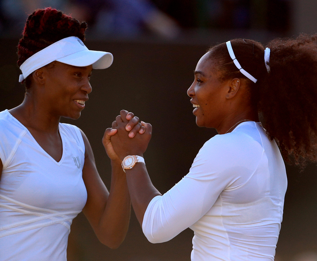 Double delight: Serena (right) and Venus Williams followed singles quarter-final success with a doubles victory at Wimbledon last night
