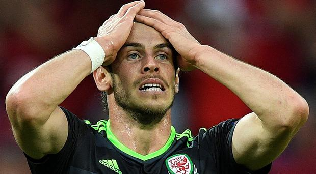 Wales' forward Gareth Bale reacts during the Euro 2016 semi-final football match between Portugal and Wales at the Parc Olympique Lyonnais stadium in Décines-Charpieu, near Lyon, on July 6, 2016. / AFP PHOTO / MARTIN BUREAUMARTIN BUREAU/AFP/Getty Images