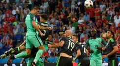 High and mighty: Ronaldo climbs above the Welsh defence to head Portugal towards a Euro final place on Sunday