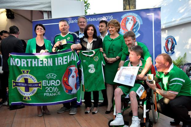 Paris' mayor Anne Hidalgo (C) flanked by Ireland Ambassador Geraldine Byrne Nason (R) holds an Ireland jersey as she gives the City of Paris medal to Republic of Ireland and Northern Ireland football supporters who came to cheer their team during the UEFA Euro 2016 in Paris, on July 7, 2016. AFP/Getty Images