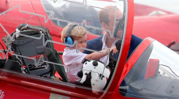 The Duke of Cambridge sits Prince George in the cockpit of an RAF Arrow aircraft, during a visit to the Royal International Air Tattoo at RAF Fairford - the world's largest military airshow. Chris Radburn/PA Wire