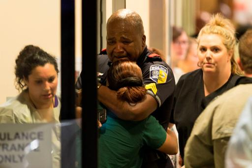A Dallas Area Rapid Transit police officer receives comfort at the Baylor University Hospital emergency room entrance Thursday, July 7, 2016, in Dallas (Ting Shen/The Dallas Morning News via AP)