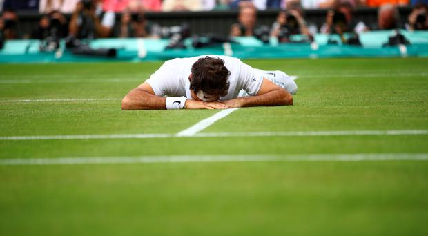 Switzerland's Roger Federer falls to the ground while trying to return to Canada's Milos Raonic. AFP/Getty Images