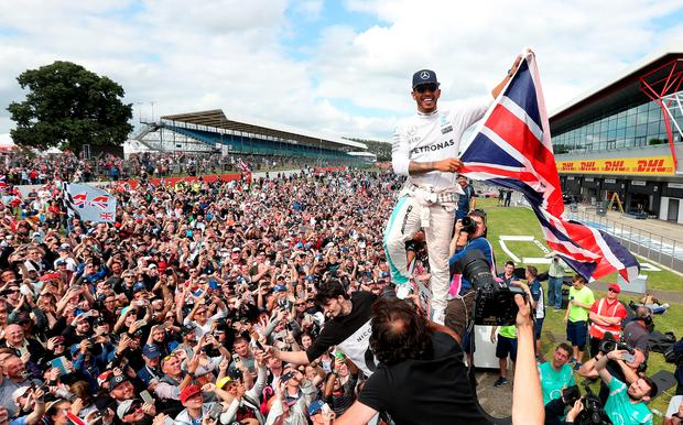 Flying the flag: Lewis Hamilton celebrates with fans after winning the British Grand Prix at Silverstone