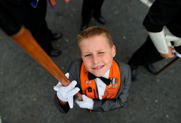 A young Orange band member looks up at the camera as he holds his banner before he takes part in the annual Orange march on July 12, 2016 in Belfast, Northern Ireland. The Orange marches and demonstrations celebrate the Battle of the Boyne in 1690 when the Protestant King William of Orange defeated the Catholic King James II on the banks of the river Boyne. (Photo by Charles McQuillan/Getty Images)