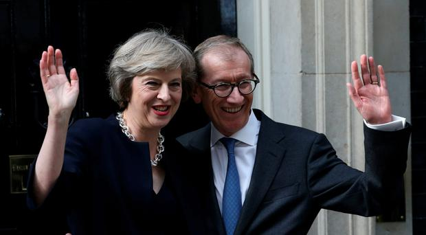 Britain's new Prime Minister Theresa May (L) and her husband Philip John May (R) wave outside the door of 10 Downing Street in central London on July 13, 2016 on the day that Theresa May takes office following the formal resignation of David Cameron. AFP/Getty Images