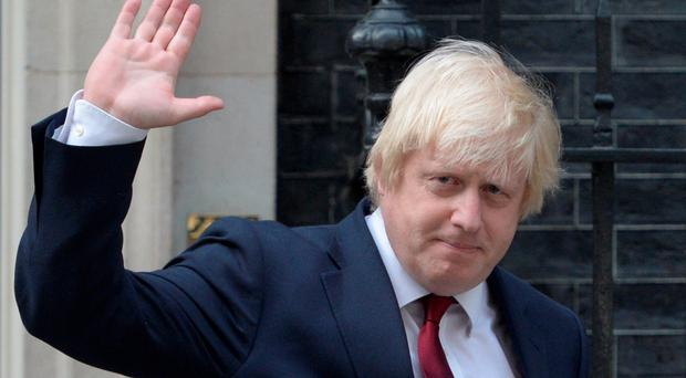 Newly appointed Foreign Secretary Boris Johnson waves as he leaves 10 Downing Street in central London on July 13, 2016 after new British Prime Minister Theresa May took office. AFP/Getty Images