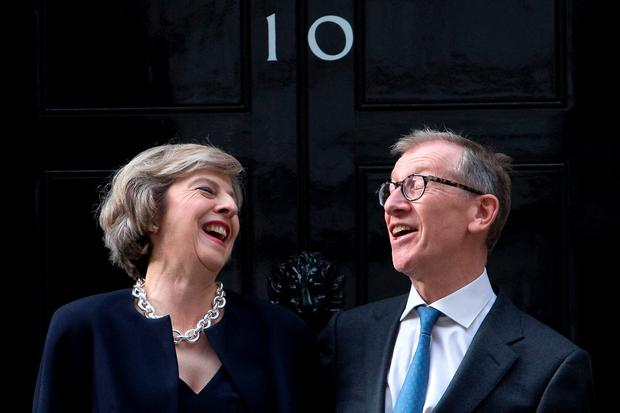 Britain's new Prime Minister Theresa May (L) and her husband Philip John May (R) laugh together outside the door of 10 Downing Street in central London on July 13, 2016 on the day that Theresa May takes office following the formal resignation of David Cameron. AFP/Getty Images
