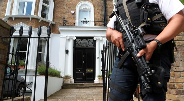 Armed police stand outside the property where former prime minister David Cameron is staying in Notting Hill in London, after leaving Downing Street yesterday. PA