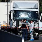 Forensics officers and policemen look for evidence near a truck on the Promenade des Anglais seafront in the French Riviera town of Nice on July 15, 2016. AFP/Getty Images