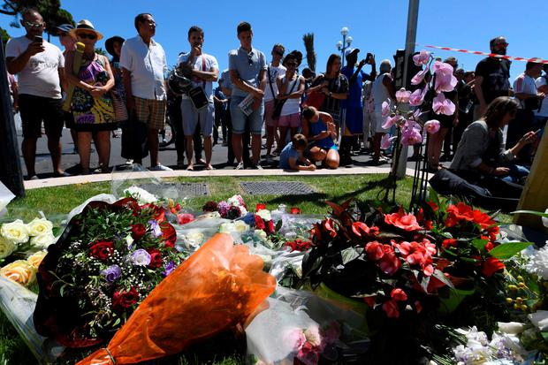 People stand on July 15, 2016 in front of flowers and candles placed near the site in Nice where a gunman smashed a truck into a crowd of revellers celebrating Bastille Day, killing at least 84 people. AFP PHOTO / BORIS HORVATBORIS HORVAT/AFP/Getty Images
