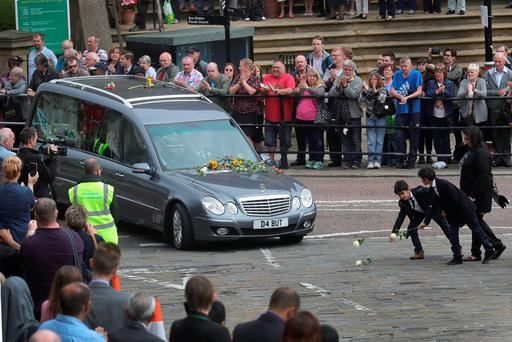 Schoolboys place flowers on the Yorkshire cobble stones as people pay their respects as the funeral cortege of murdered member of parliament Jo Cox processes through Batley Market Place in her constituency on July 15, 2016 in Batley, England. (Photo by Christopher Furlong/Getty Images)