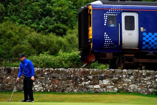 Branch line: A train driver slows down to watch Rory McIlroy line up a putt on the 11th green during the second round of The Open at Troon