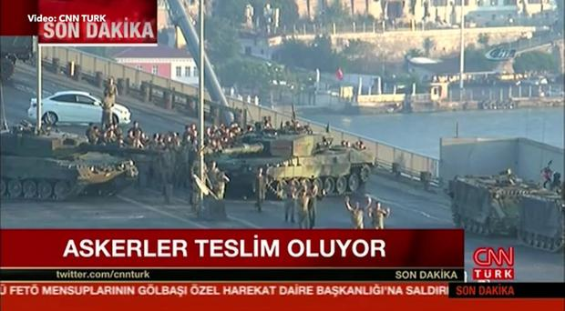 THIS is the moment soldiers blocking a bridge in Turkey held up their hands in surrender hours after staging a military coup.