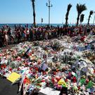 People gather beside flowers at a makeshift memorial near the Promenade des Anglais in Nice