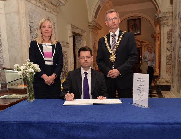 The new secretary of state for Northern Ireland James Brokenshire signs a book of condolence in Belfast City Hall on Monday with Lord Mayor Brian Kingston and Suzanne Wylie (Chief executive of Belfast City Council) for the victims of the Nice attack Pic Pacemaker / Belfast City Council