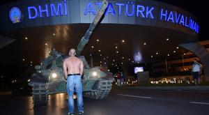 A man stands in front of a tank in the entrance to Istanbul's Ataturk airport, early Saturday, July 16, 2016. Members of Turkey's armed forces said they had taken control of the country, but Turkish officials said the coup attempt had been repelled early Saturday morning in a night of violence, according to state-run media. (Ismail Coskun/IHA via AP)